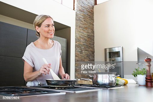 Middle-aged woman cooking dinner : Bildbanksbilder