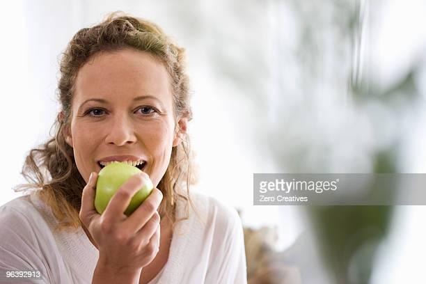 middle-aged woman eating a apple