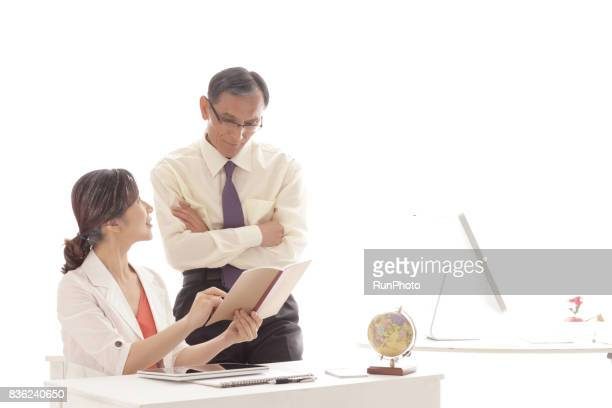 middle-aged woman explaining to a middle-aged man with a note in hand