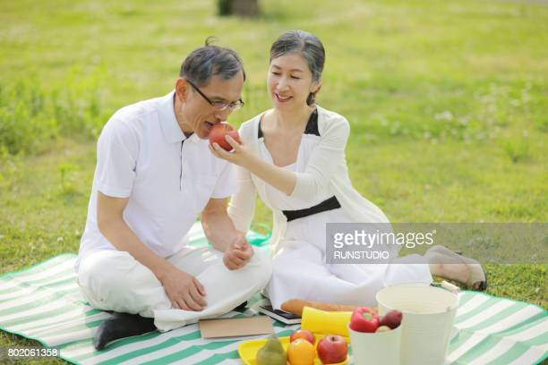 middle-aged woman giving a red apple to a middle-aged man