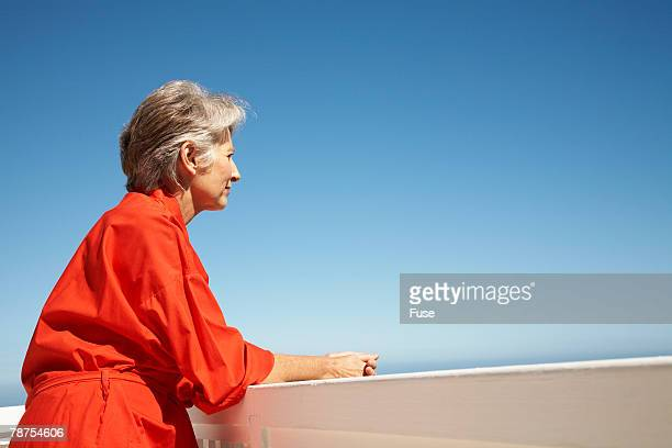 Middle-Aged Woman in Orange Robe Thinking on Balcony