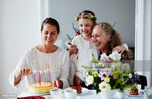 middle-aged woman light the candles of a birthday cake