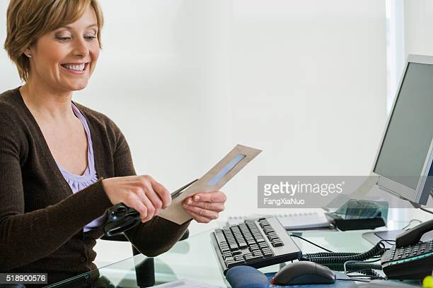 Middle-aged woman looking at bills at computer