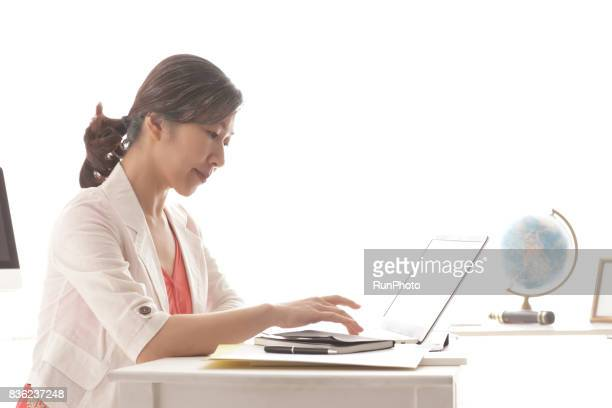 middle-aged woman operating a laptop computer