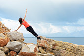 A middle-aged woman doing fitness exercises on the stone coast of the sea during the holiday season.
