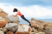 A woman doing an exercise for fitness on the stone sea coast of Turkey in the holiday season.