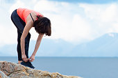 A woman ties up her shoelaces on sports shoes for fitness on the seashore.