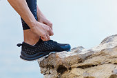A woman in the mountains ties up the shoelaces of the sneakers for fitness. Sports lifestyle.