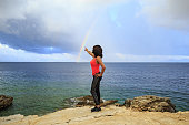 A middle-aged woman enjoys loneliness after exercising. She draws a rainbow over the sea after fitness.
