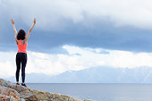 The woman raised her hands up on the beach. She is wearing sports clothes for fitness.