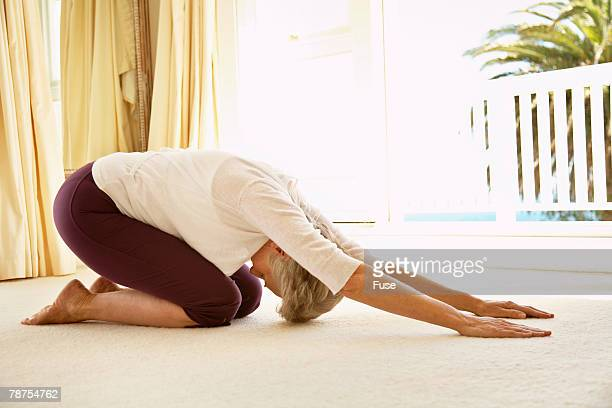 Middle-Aged Woman Stretching on Floor