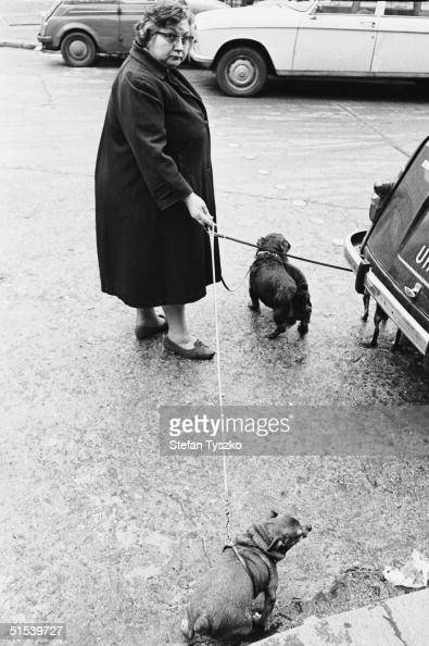 A middleaged woman takes her two dogs for a walk in a Paris street circa 1970