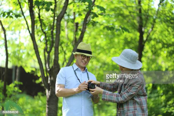 middle-aged woman teaching middle-aged men how to use the camera