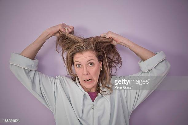 Middle-aged woman tearing her hair out