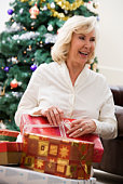 Middle-aged woman unwrapping presents