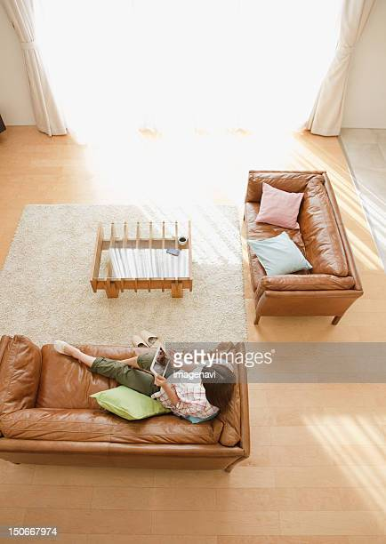 Middle-aged woman using a tablet PC on a sofa
