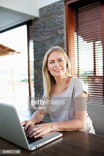 Middle-aged woman using laptop at home : Stock Photo