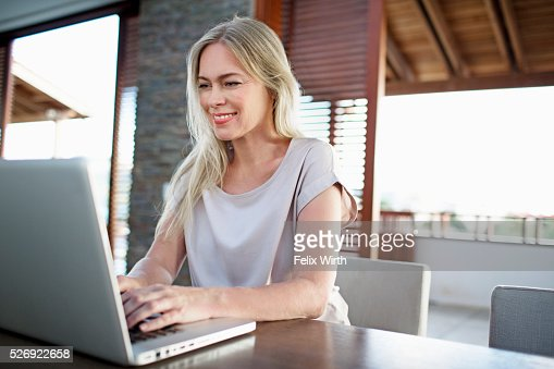 Middle-aged woman using laptop at home : Stock-Foto