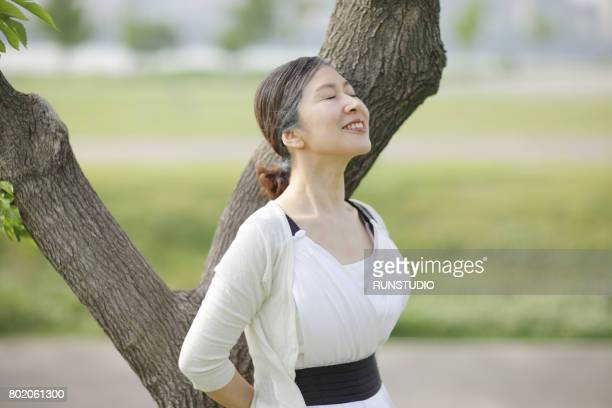 middle-aged woman who closes his eyes close to a tree