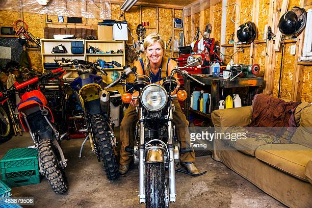 Middle-aged woman with motorcycles in her garage.