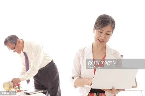 Middle-aged women who have laptop computers and middle-aged men who are touching the globe