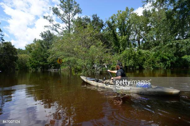 Middleburg resident Emmett Kesler uses his canoe to check in on locals remaining in the severe flooded area of Black Creek in Middleburg Florida USA...