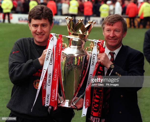 AND ASSISTANT MANAGER BRIAN KIDD HOLD THE PREMIERSHIP TROPHY AFTER THEIR SIDE BEAT Middlesbrough TO WIN THE TITLE AT RIVERSIDE STADIUM 03/12/98 Kidd...