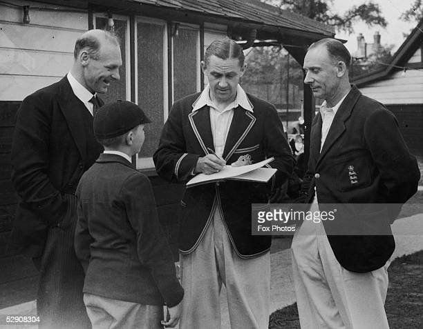 Middlesex and England bowler Gubby Allen George Oswald Browning Allen signing an autograph for a young fan He is with fellow cricketer Jack Hobbs and...