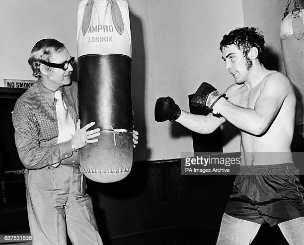 Middleweight Alan Minter right hones his skills on the bag held by promoter Mike Barratt left