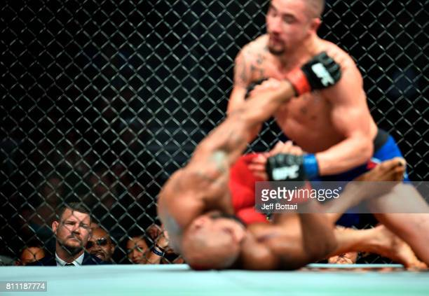Middleweight Champion Michael Bisping of England watches as Yoel Romero of Cuba and Robert Whittaker of New Zealand exchange punches in their interim...