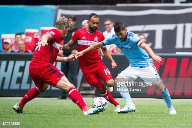 Midfielder Bastian Schweinsteiger of Chicago Fire and forward David Villa of New York City FC vie for the ball during the match at Yankee Stadium on...