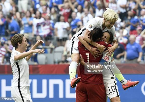 USA midfielder Carli Lloyd is congratuled by goalkeeper Hope Solo and midfielder Megan Rapinoe after scoring a goal during the final football match...
