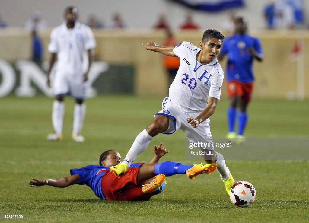 Midfielder Jean Monuma Constant #13 of Haiti attempts a slide tackle on a ball controlled by defender Jorge Claros #20 of Honduras during the second half of a 2013 CONCACAF Gold Cup soccer match on July 8, 2013 at Red Bull Arena in Harrison, New Jersey. Honduras defeated Haiti 2-0.