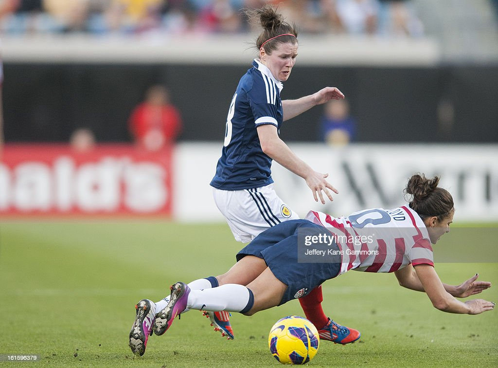 Midfielder Kim Little #8 of Scotland trips up Midfielder Carli Lloyd #10 of the United States during the game at EverBank Field on February 9, 2013 in Jacksonville, Florida.