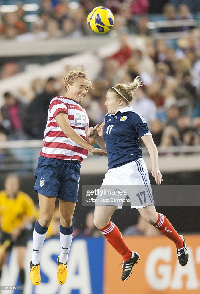 Midfielder Kristie Mewis #23 of the United States and Defender Frankie Brown #17 of Scotland go in to head the ball during the game at EverBank Field on February 9, 2013 in Jacksonville, Florida.