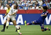 USA midfielder Lauren Holiday shots in front of Japan's defender Saori Ariyoshi during the 2015 FIFA Women's World Cup final between the USA and...