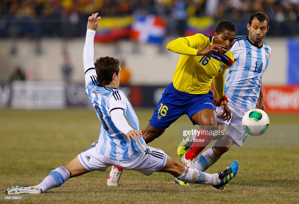 Midfielder Luis <a gi-track='captionPersonalityLinkClicked' href=/galleries/search?phrase=Antonio+Valencia&family=editorial&specificpeople=543830 ng-click='$event.stopPropagation()'>Antonio Valencia</a> #16 of Ecuador battles for the ball against midfielder <a gi-track='captionPersonalityLinkClicked' href=/galleries/search?phrase=Javier+Mascherano&family=editorial&specificpeople=490876 ng-click='$event.stopPropagation()'>Javier Mascherano</a> #14 and forward <a gi-track='captionPersonalityLinkClicked' href=/galleries/search?phrase=Augusto+Fernandez&family=editorial&specificpeople=684736 ng-click='$event.stopPropagation()'>Augusto Fernandez</a> #8 of Argentina at MetLife Stadium on November 15, 2013 in East Rutherford, New Jersey.