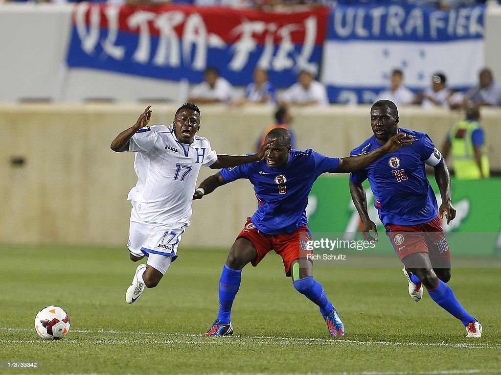 Midfielder Marvin Chavez #17 of Honduras is challenged by forward Kervens Belfort #9 and midfielder Jean-Marc Alexandre #16 of Haiti during a 2013 CONCACAF Gold Cup soccer match on July 8, 2013 at Red Bull Arena in Harrison, New Jersey. Honduras defeated Haiti 2-0.