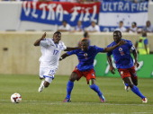 Midfielder Marvin Chavez of Honduras is challenged by forward Kervens Belfort and midfielder JeanMarc Alexandre of Haiti during a 2013 CONCACAF Gold...