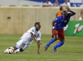 Midfielder Marvin Chavez of Honduras is challenged by forward Kervens Belfort of Haiti during a 2013 CONCACAF Gold Cup soccer match on July 8 2013 at...