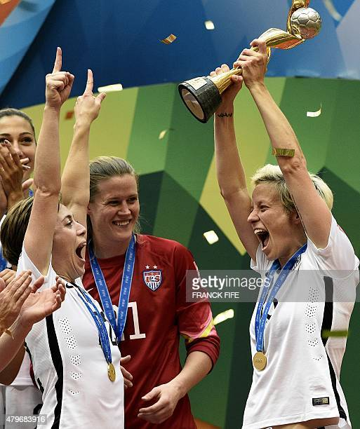 USA midfielder Megan Rapinoe holds the trophy next to USA defender Meghan Klingenberg as he celebrates with teammates after their victory in the...