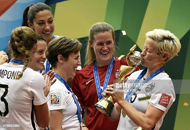 USA midfielder Megan Rapinoe kiss the trophy next to USA defender Meghan Klingenberg as she celebrates with teammates after their victory in the...