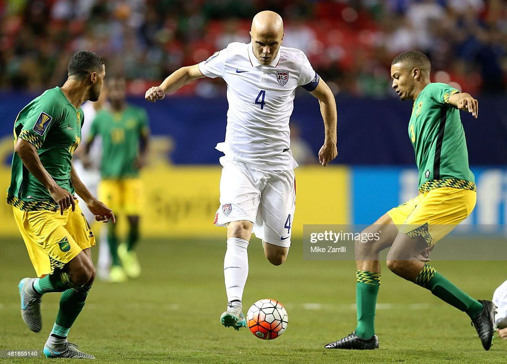 Midfielder <a gi-track='captionPersonalityLinkClicked' href=/galleries/search?phrase=Michael+Bradley+-+Soccer+Player&family=editorial&specificpeople=7022299 ng-click='$event.stopPropagation()'>Michael Bradley</a> #4 of the United States Jamaica dribbles between defenders during the 2015 CONCACAF Gold Cup semifinal match against Jamaica at Georgia Dome on July 22, 2015 in Atlanta, Georgia.
