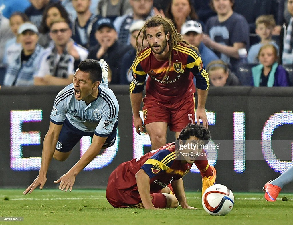 Mid-fielder Roger Espinoza #27 of Sporting Kansas City reacts after getting fouled by defender Tony Beltran #2 of Real Salt Lake as Kyle Beckerman #5 looks on during the first half on April 11, 2015 at Sporting Park in Kansas City, Kansas.