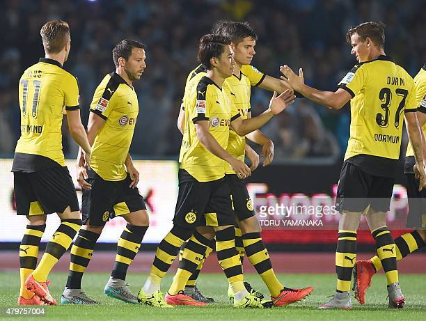 Midfielder Shinji Kagawa of Germany's football club Borussia Dortmund is congratulated by his teammates just after scoring his first goal against...