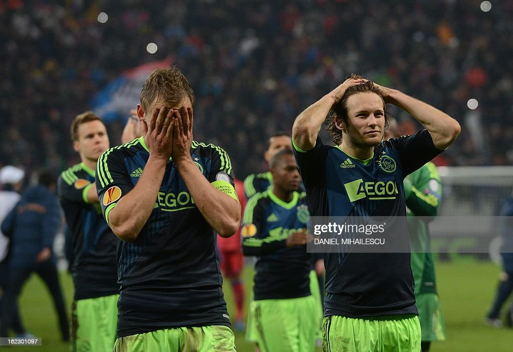 midfielder Siem de Jong (L) and defender Daley Blind (R) of Ajax Amsterdam looks dejected at the end of penalties kicks as Steaua Bucharest qualifies during UEFA Europa League Round of 32 football match in Bucharest February 21, 2013.