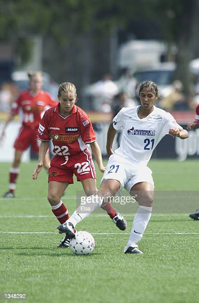 Midfielder Steffi Jones of the Washington Freedom dribbles the ball while being pursued by midfielder Mandy Clemens of the Philadelphia Charge on...