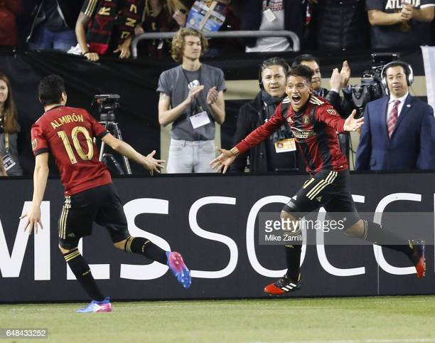 Midfielder Yamil Asad of Atlanta United celebrates with midfielder Miguel Almiron after Asad scores the first goal of the game and the first goal in...