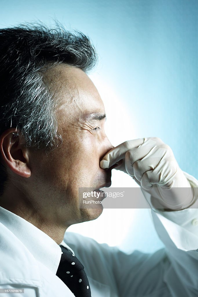 midle age doctor holding nose : Stock Photo
