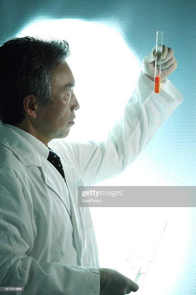 midle age doctor looking at test tube : Stock Photo